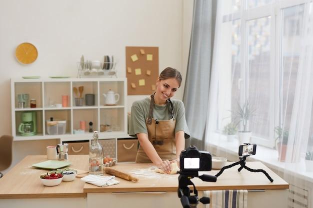 Une jeune blogueuse prépare un gâteau et le tourne sur la vidéo pour son contenu dans la cuisine domestique