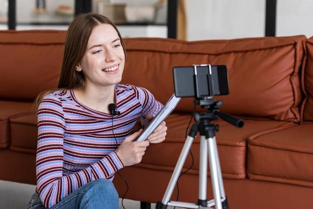 Jeune blogueuse s'enregistrant avec smartphone