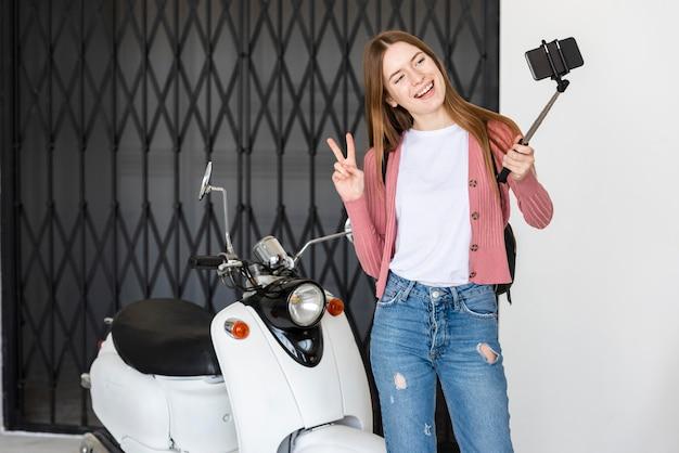 Une jeune blogueuse s'enregistre à côté d'une moto