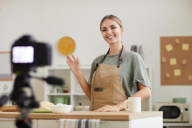 Jeune blogueuse souriante et filmant la vidéo qu'elle apprend à cuisiner en ligne