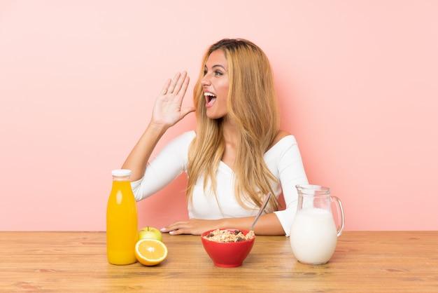 Jeune, blond, femme, avoir, petit déjeuner, lait, cris, bouche grande ouverte
