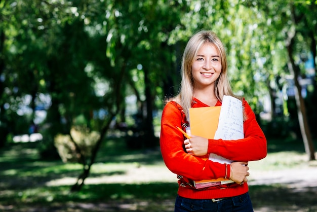 Jeune blonde avec carnet dans le jardin