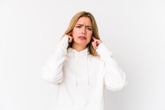 Jeune blonde caucasienne femme isolée couvrant les oreilles avec les doigts, stressée et désespérée par une forte ambiance.