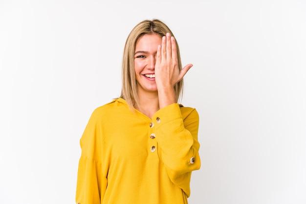 Jeune blonde caucasienne femme isolée s'amuser couvrant la moitié du visage avec la paume.