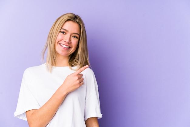Jeune blonde caucasienne femme isolée souriant et pointant de côté, montrant quelque chose à l'espace vide.