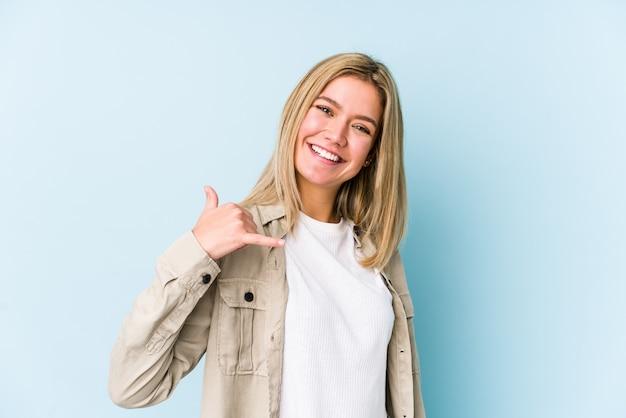Jeune blonde caucasienne femme montrant un geste d'appel de téléphone mobile avec les doigts.