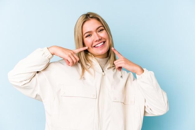 Jeune blonde caucasienne femme sourit, pointant les doigts sur la bouche.