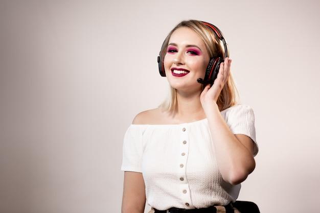 Jeune blonde femme opérateur dans les écouteurs sur fond clair. maquette