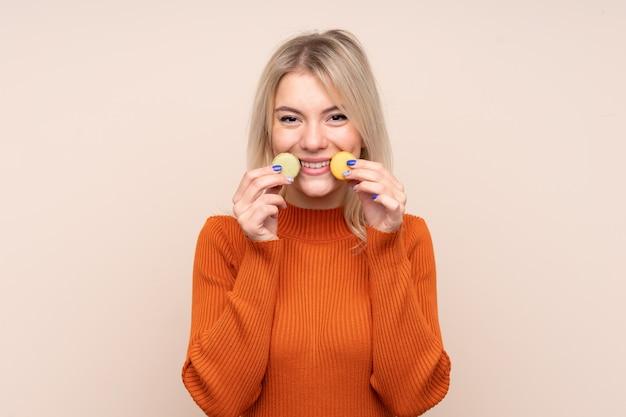 Jeune blonde femme russe sur un mur isolé tenant des macarons français colorés et souriant