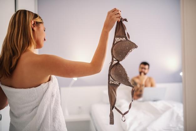 Jeune blonde passionnée enveloppée dans une serviette tenant un soutien-gorge et séduisant son petit ami