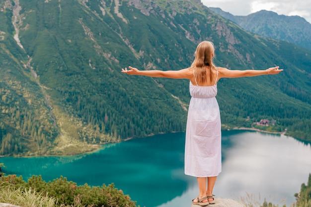 Jeune blonde en robe blanche debout à pierre dans les montagnes avec les mains écartées et le magnifique lac derrière.