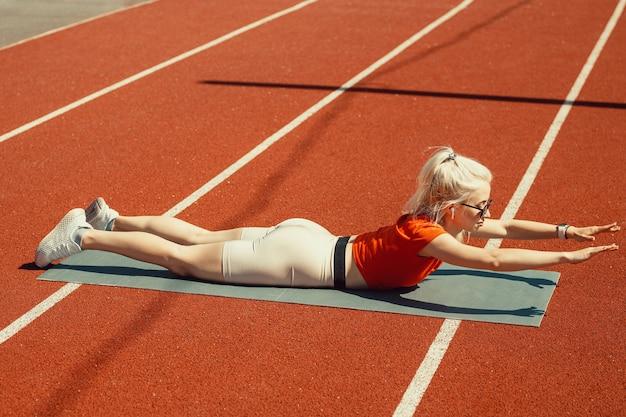 Jeune blonde secoue les muscles abdominaux sur un tapis de sport dans la rue