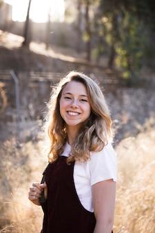 Jeune blonde souriante et regardant la caméra