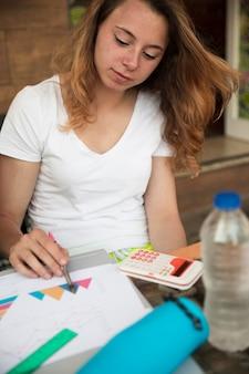 Jeune blonde travaillant avec des diagrammes près de la calculatrice