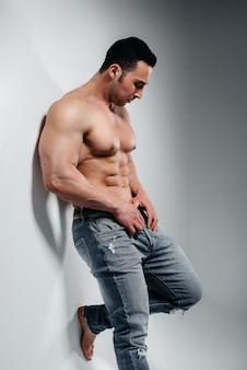 Un jeune bodybuilder athlète pose dans le studio seins nus en jeans près du mur