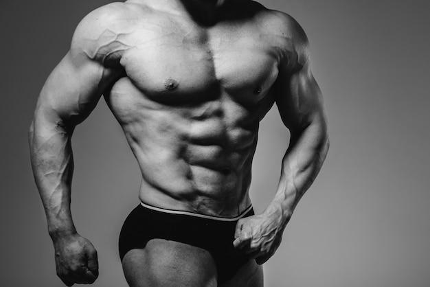 Un jeune bodybuilder athlète pose dans le studio seins nus, montrant ses abdominaux et ses muscles