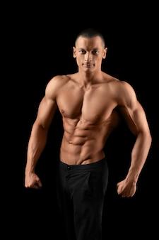 Jeune bodybuilder attrayant posant torse nu souriant