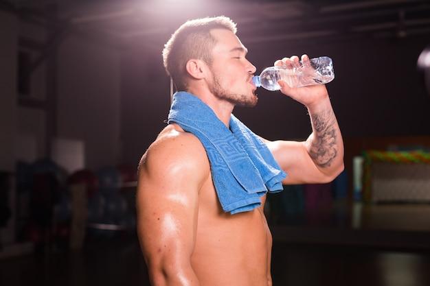 Jeune bodybuilder dans la salle de gym boire une bouteille d'eau