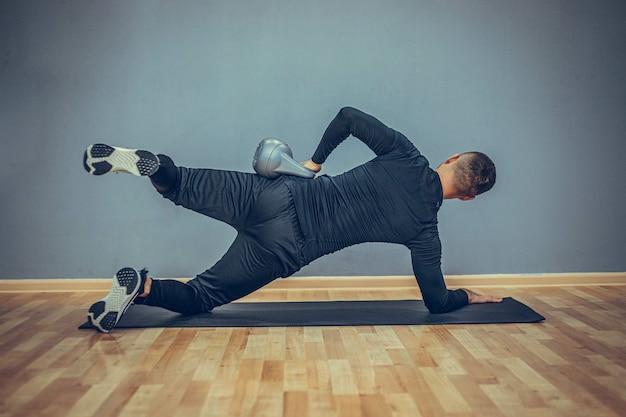 Jeune bodybuilder faisant de l'exercice avec kettlebell