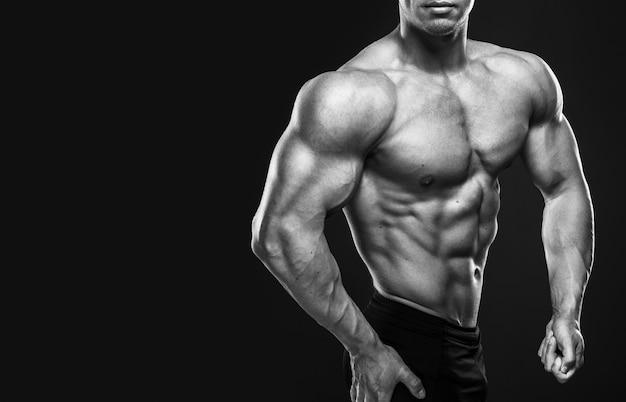 Jeune bodybuilder montrant ses muscles en studio