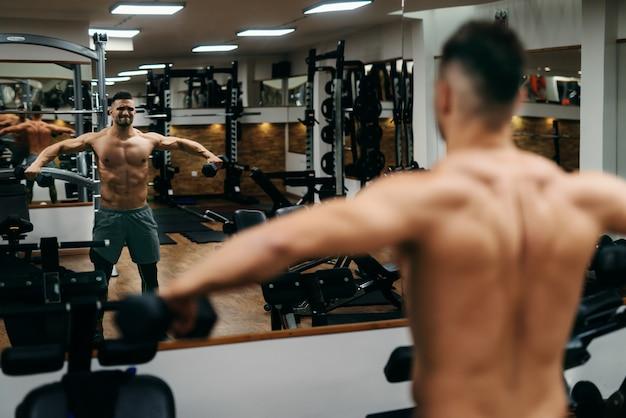 Jeune bodybuilder torse nu, faire des exercices avec des haltères en se tenant debout dans la salle de gym