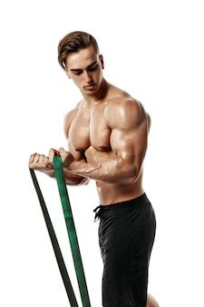 Jeune bodybuilder travaillant avec élastique sur fond blanc