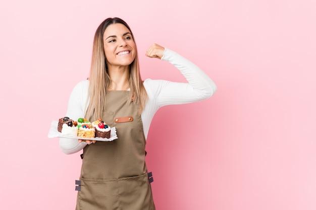 Jeune boulanger femme tenant des bonbons levant le poing après une victoire, concept gagnant.