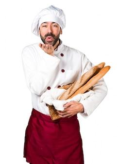 Le jeune boulanger prend du pain et envoie un bisou