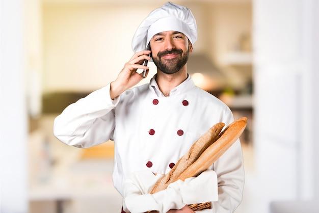 Le jeune boulanger prend du pain et parle au mobile dans la cuisine