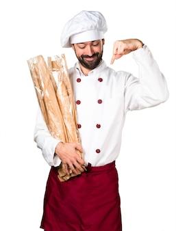 Le jeune boulanger prend du pain et pointe vers le bas