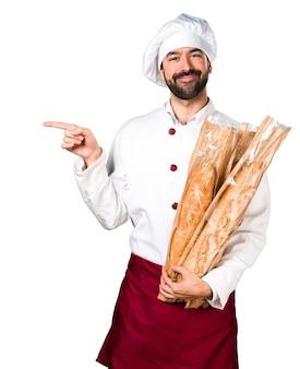 Le jeune boulanger prend du pain et pointe vers le côté