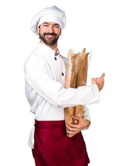 Le jeune boulanger prend du pain et pointe vers le haut