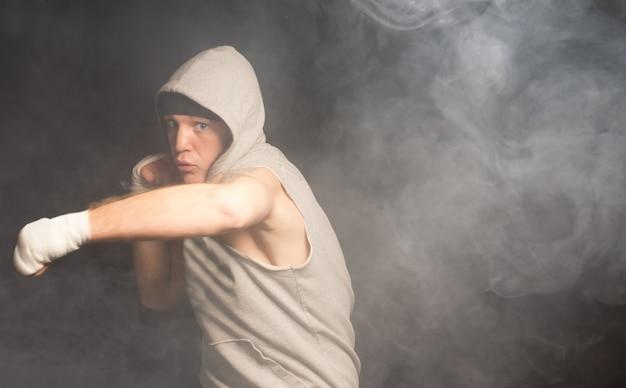 Jeune boxeur agile jetant son poids derrière un coup de poing avec un regard de détermination sombre dans un environnement sombre et enfumé