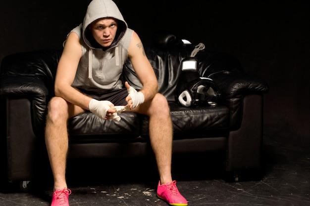 Jeune boxeur assis pensant et attendant son tour sur le ring assis sur un canapé noir