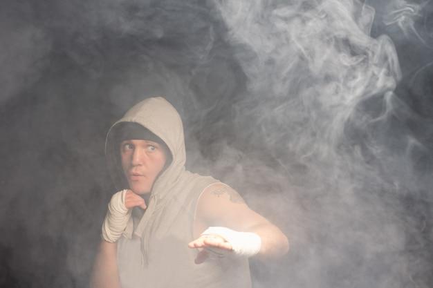 Jeune boxeur aux poings bandés portant un haut à capuchon combats dans une pièce sombre et enfumée