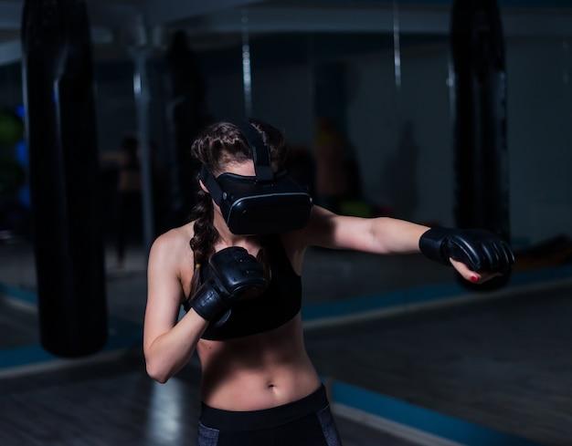 Jeune boxeur de combat fit fille dans des lunettes vr portant des gants de boxe en formationjeu futuriste