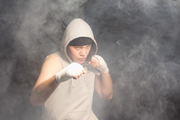 Jeune boxeur combattant dans une atmosphère remplie de fumée noire