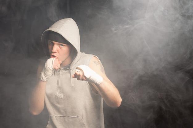 Jeune boxeur combattant avec des poings bandés dans un environnement sombre et enfumé portant un haut à capuchon gris