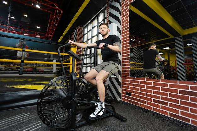 Jeune boxeur masculin athlétique s'entraîne sur un vélo d'exercice près du ring.