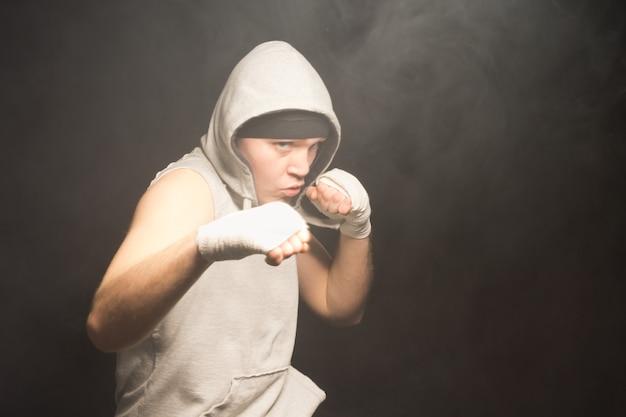 Jeune boxeur pugnace portant un haut à capuche levant ses poings bandés dans un combat dans une atmosphère sombre et enfumée avec fond