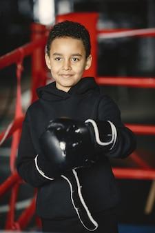 Jeune boxeur travailleur apprenant à boxer. enfant au centre sportif. enfant prenant un nouveau passe-temps