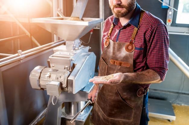 Un jeune brasseur dans un tablier en cuir contrôle le broyage des graines de malt dans un moulin d'une brasserie moderne