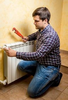 Jeune bricoleur fixant le radiateur de chauffage avec une pince plombier rouge