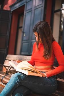 Jeune brune assise sur un banc dans le parc en lisant un livre