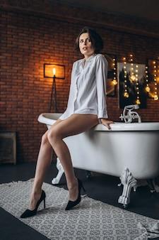 Une jeune brune assise sur le bord de la baignoire et regarde la caméra.