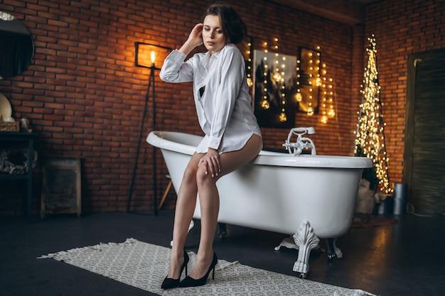Une jeune brune assise sur le bord de la baignoire