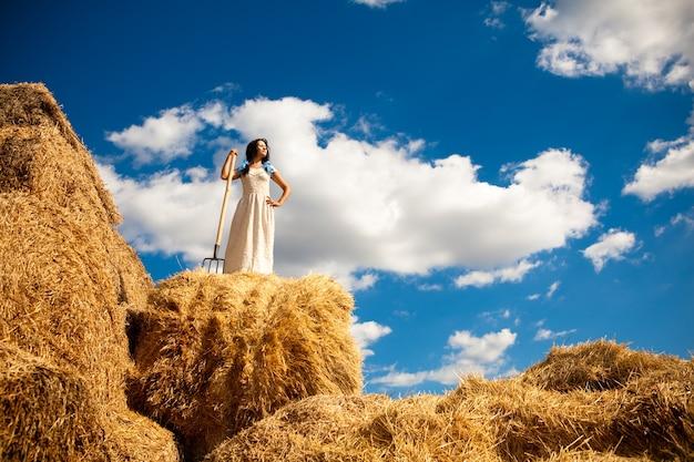 Jeune brune dans une robe blanche se dresse avec une fourche à foin dans un champ par une claire journée d'été