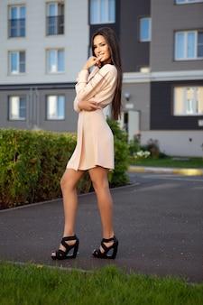 Une jeune brune dans une robe d'été légère pose dans la rue