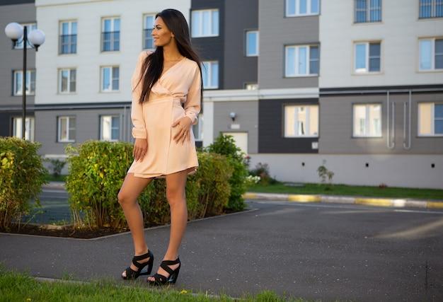 Une jeune brune dans une robe légère d'été est debout dans la rue en souriant