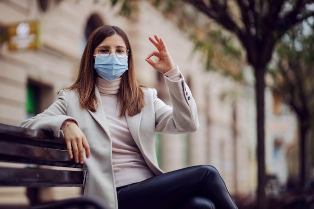 Jeune brune avec un masque facial assis sur le banc à l'extérieur et montrant un geste correct. millennials pendant l'épidémie corona.